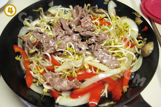 Đổ thịt bò đã xào tái vào trộn lại và nêm nếm gia vị