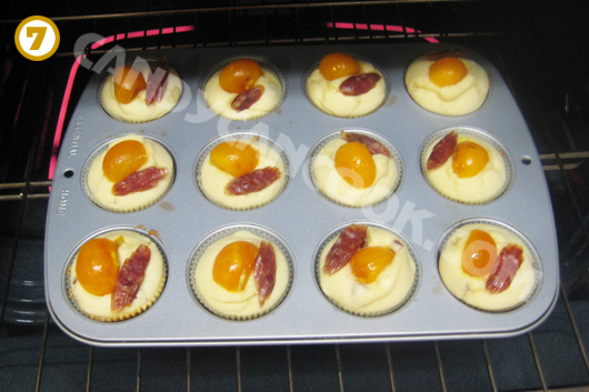 Xếp trứng muối và lạp xưởng lên bề mặt bánh khi bánh đã bắt đầu đứng dáng